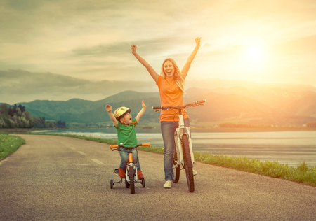 family exercise: Happiness Mother and son on the bicycles funning outdoor Stock Photo