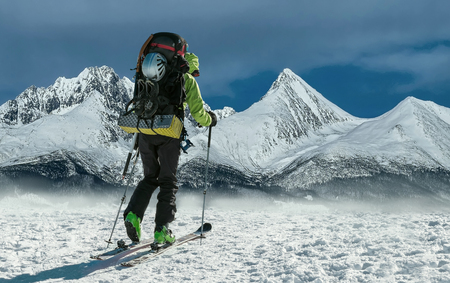 sunny cold days: Men with backpack at ski goes to the top of mountain in sun day