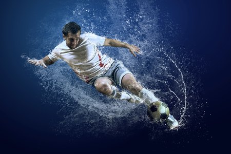 association: Splash of drops around football player under water Stock Photo