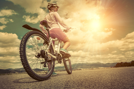 sun glasses: Beautiful woman in helmet and glasses stay on the bicycle under sky with clouds.
