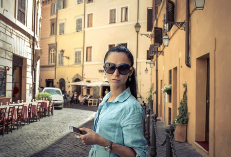 people travelling: Female tourist shoot by phone on the Roman street.