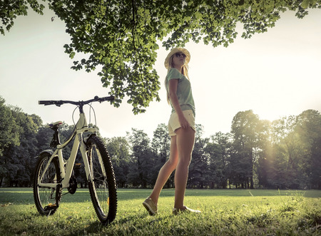 non urban scene: Woman under sun light at day near her bicycle in the park Stock Photo
