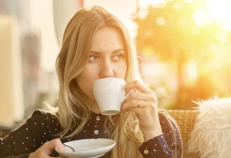 美しい金髪女性ドリンク カフェでコーヒー 写真素材