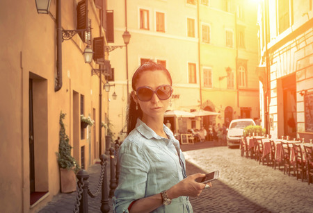 life style: Female tourist shoot by phone on the Roman street.