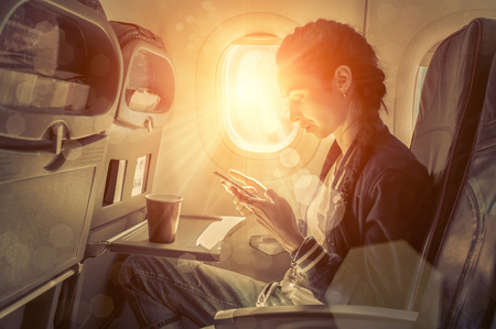 people travelling: Woman sitting at airplane and looking to mobil phone.