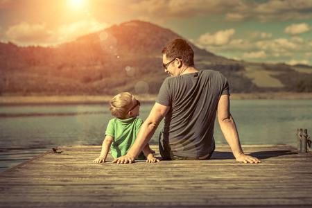 jezior: Ojciec i syn na szczęście molo w słoneczny dzień pod działaniem promieni słonecznych.