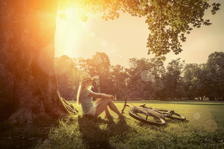 Woman sitting under sun light at day near her bicycle in the park Standard-Bild