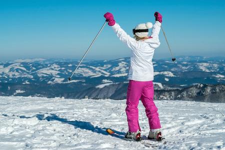 Female an Ski-Aufenthalt auf dem Gipfel des Berges mit schöner Aussicht Standard-Bild