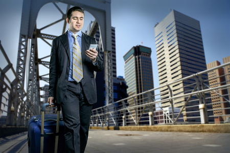 business man phone: Man with baggage speaking by phone on the bridge