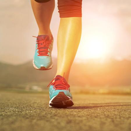 running: Runner athlete feet running on road under sunlight. Stock Photo