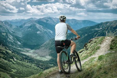 bicicleta: Los hombres con bicicleta Aroun montañas hermosa vista. Foto de archivo