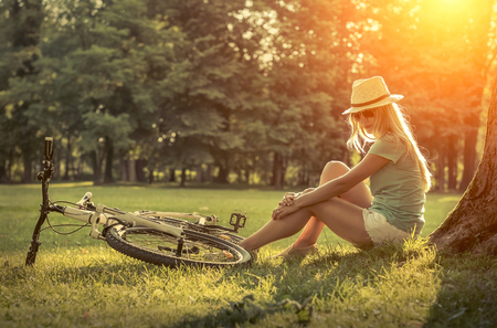 non urban 1: Woman sitting under sun light at day near her bicycle in the park Stock Photo