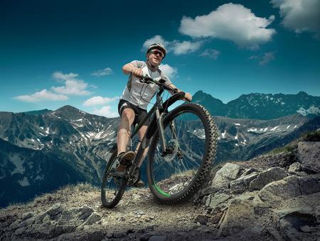 헬멧과 안경에 남자가 구름과 하늘 아래 자전거에 머물.
