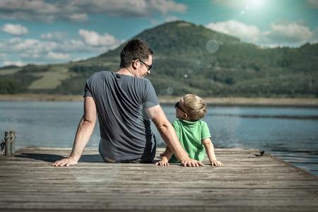 dia soleado: Felicidad padre e hijo en el muelle en día soleado bajo la luz solar.