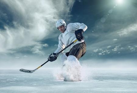 hockey hielo: Jugador de hockey sobre hielo al aire libre en la acción alrededor de las montañas