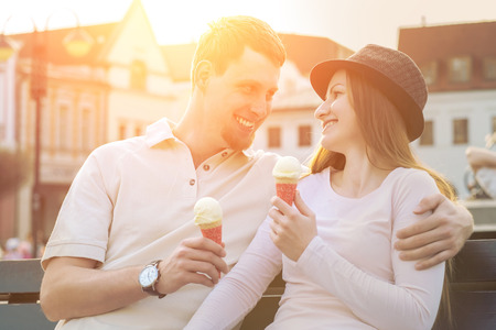 people   lifestyle: Happiness couple with ice cream sitting at street under sunlight