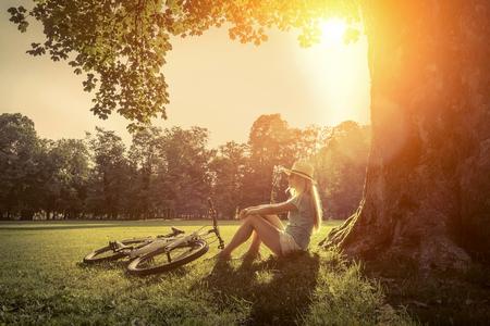 여자가 공원에서 그녀의 자전거 근처에서 태양 빛 아래 앉아 스톡 콘텐츠