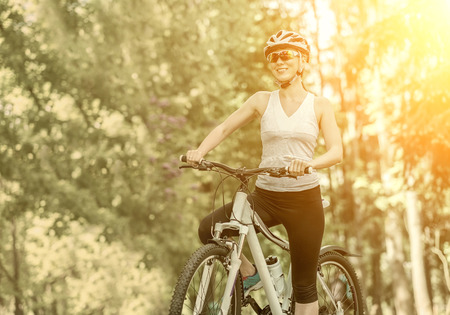 individual sports: Portrait of beautiful woman on the bicycle in the park. Stock Photo