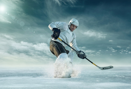 Ice hockey player in action outdoor around mountains Reklamní fotografie - 47236996