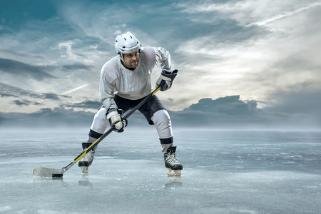 hockey skates: Ice hockey player on the ice in mountains Stock Photo