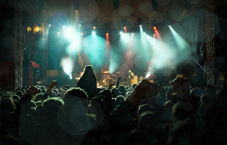 Rock concert, silhouettes of happy people raising up hands