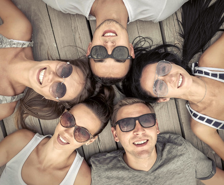 Portrait of group friends on the wooden background. Stock Photo