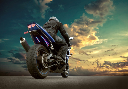 Man seat on the motorcycle under sky with clouds Reklamní fotografie - 48086051