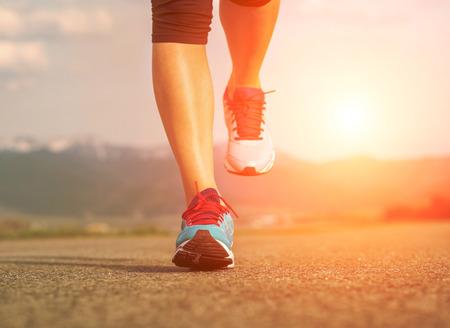 corriendo: Pies Runner atleta que se ejecutan en el camino bajo la luz del sol.