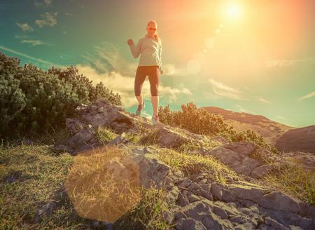woman running: Female running in mountains under sunlight. Stock Photo