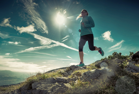 mujeres corriendo: Mujer corriendo en montañas bajo la luz del sol. Foto de archivo