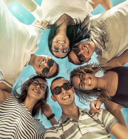 group of friends: Group of friends on the beach under sunlight. Stock Photo