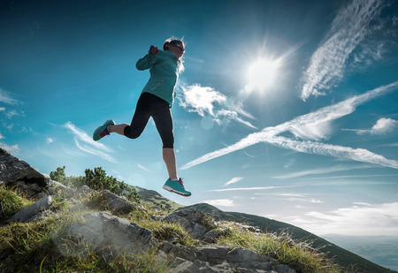 Female running in mountains under sunlight. Stock fotó
