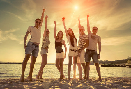 Friends funny dance on the beach under sunset sunlight. Reklamní fotografie - 48723104