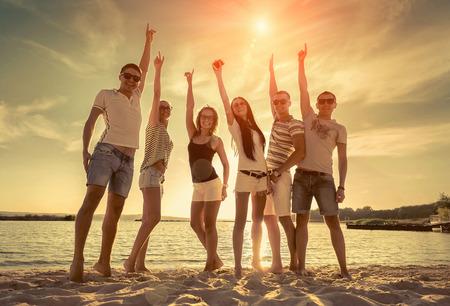 beautiful location: Friends funny dance on the beach under sunset sunlight.