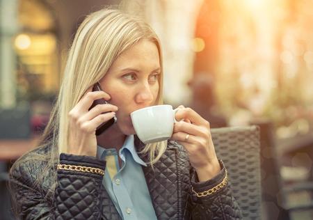 cafe internet: Asiento de la mujer en caf� con su tel�fono y caf�. Foto de archivo
