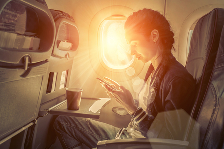 women: Woman sitting at airplane and looking to mobil phone.
