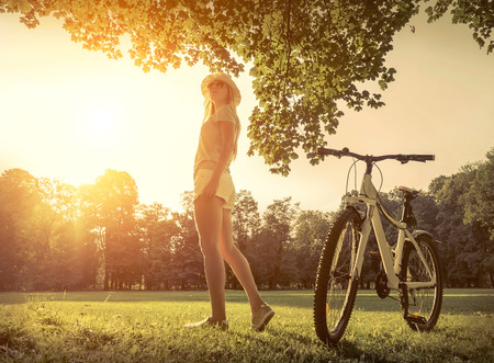 non urban 1: Woman under sun light at day near her bicycle in the park Stock Photo