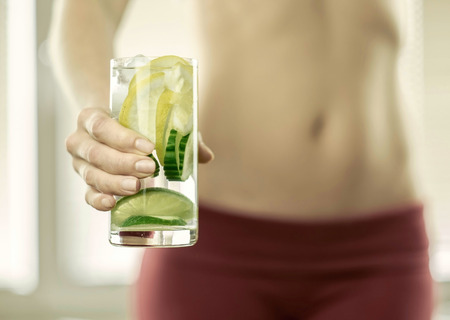 lemon water: Healthy coctail in the hands of fitness female.