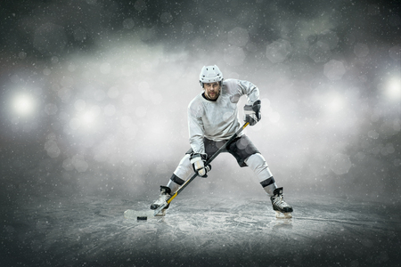 ice hockey puck: Ice hockey player on the ice, outdoors