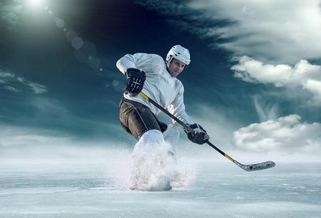 Giocatore di hockey su ghiaccio in azione esterna intorno montagne Archivio Fotografico - 48722912