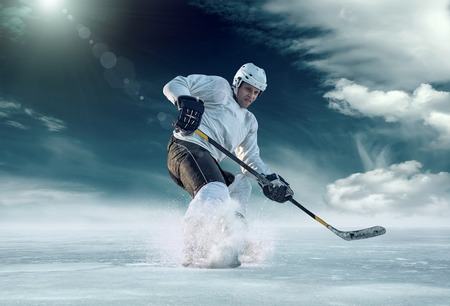 Ice hockey player in action outdoor around mountains Фото со стока - 48722912