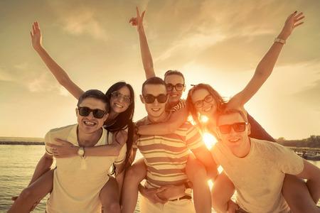 Friends fun on the beach under sunset sunlight.