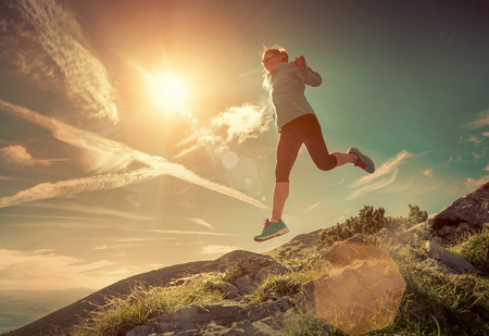 the nature of sunlight: Female running in mountains under sunlight. Stock Photo