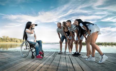sunlight: Disabled Female photographer shooting her friends under sunlight.