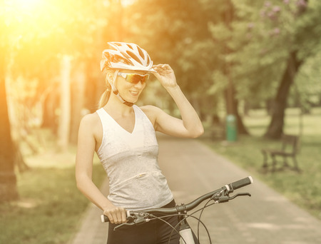 recreational: Portrait of beautiful woman on the bicycle in the park. Stock Photo