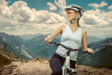 stay beautiful: Beautiful woman in helmet and glasses stay on the bicycle around mountains.