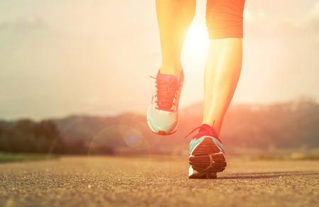 and athlete: Pies Runner atleta que se ejecutan en el camino bajo la luz del sol.