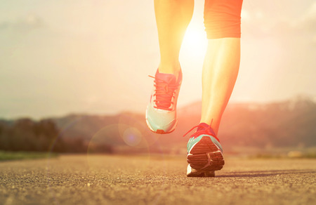 adult foot: Runner athlete feet running on road under sunlight. Stock Photo
