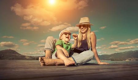 행복 어머니와 햇빛 아래 화창한 날에 부두에 아들.