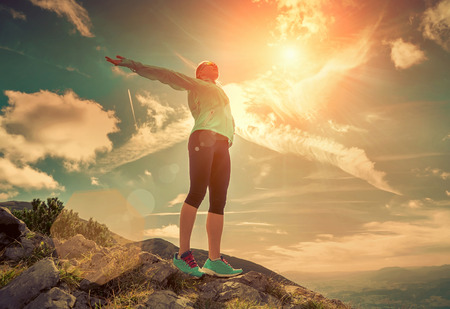 sports: Female stay on the top of mountain under sunlight.